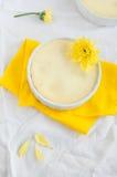 Käsekuchen und Blume auf gelber Serviette und weißer Tischdecke Lizenzfreie Stockfotos