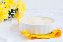 Käsekuchen und ein Blumenstrauß von gelben Blumen Stockfoto