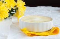 Käsekuchen und ein Blumenstrauß von gelben Blumen lizenzfreie stockfotografie