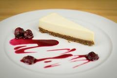 Käsekuchen von der weißen Schokolade auf weißer Platte Stockfotografie