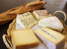 Käsemehrlagenplatte und ein Taktstockbrot Stockfotografie