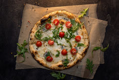 Käsepizza mit Papier und Tomate auf Draufsicht des dunklen hölzernen Hintergrundes stockbilder