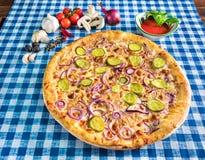Käsepizza mit roter Zwiebel und in Essig eingelegter Gurke stockfoto