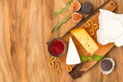 Käseplatte diente mit Stau, Feigen, Crackern und Kräutern auf einem hölzernen Hintergrund Stockfotos