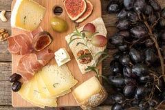 Käseplatte mit Stücken schimmeliger Käse, Prosciutto, in Essig eingelegte Pflaume stockbild