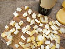 Käsestücke und -Weinprobe Auf rustikalem grobem Sackzeug Jutefaser, Leinwand Stockfoto