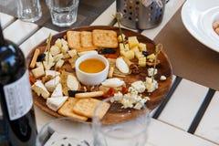 Käsevielzahl, Honig, Rotwein und Crackerkekse stockfoto