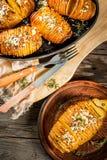 Käsige Hasselback-Kartoffel mit frischen Kräutern Lizenzfreies Stockfoto