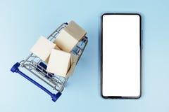 Kästen in einem Einkaufswagen oder in einer Laufkatze und mobiler Smartphone lokalisierter Hintergrund für die Einfügung des Mode stockbild
