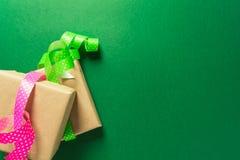 Kästen im Kraftpapier mit Bändern über grünem Hintergrund stockfoto