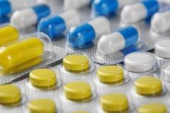 Kästen mit gelben medizinischen Pillen und blau-weißen Pillen Lizenzfreie Stockbilder
