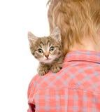 Kätzchen, das über der Schulter eines Kindes lugt lokalisiert auf weißem b Stockfotografie