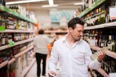 Käufer, der Alkohol-Flasche anhält Stockbild