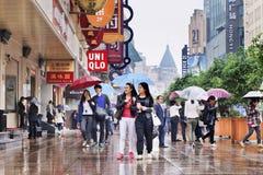Käufer mit Regenschirm in nasser Nanjing-Oststraße, Shanghai, China lizenzfreie stockfotos
