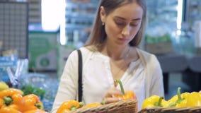 Käufer wählen die gelben Pfefferprodukte und setzen Tasche in Gemüseshop ein stock footage