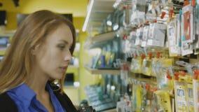 Käufer wählt sorgfältig Zubehör für Handy vor stock footage