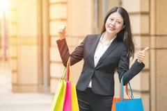 Käuferfrau im Stadteinkaufen greift herauf Haben des Spaßes ab Lizenzfreies Stockbild