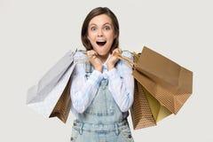 Käufermädchen, das Haufen von den Einkaufstaschen lokalisiert auf Grau hält stockfotos