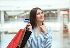 Käufermädchen, das Kreditkarte halten und Einkaufstaschen, die oben schauen lizenzfreie stockfotos
