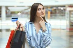 Käufermädchen, das Kreditkarte halten und Einkaufstaschen, die oben schauen lizenzfreie stockbilder