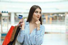 Käufermädchen, das Kreditkarte halten und Einkaufstaschen, die oben schauen stockfotos