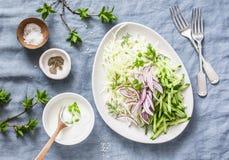 Kål gurka, röd lök, grekisk yoghurt, kålsalladsallad på en blå bakgrund, bästa sikt Lekmanna- lägenhet Detoxen bantar mat arkivbild