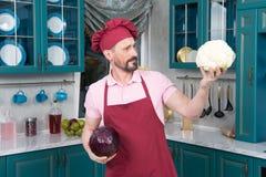Kål och kock för blomkål bättre instämde röd Mannen visar den stora blomkålen för ångamatlagning Mannen rymmer grönsaker i händer royaltyfri foto