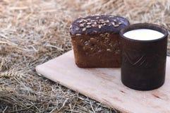 Kéfir en una taza de la arcilla con pan al aire libre Foto de archivo libre de regalías