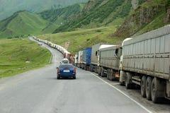 Kö av lastbilar som väntar i linjen för gränstullkontroll Arkivbilder
