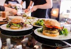 Köche, die Teller des strengen Vegetariers vorbereiten Stockbilder