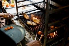 Köche grillten Fleisch auf Feuer Stockfotos