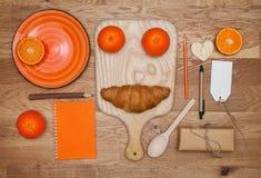 Kökåtlöje upp Apelsin: mandarin platta, blyertspenna, anteckningsbok, på en träyttersida Arkivfoton