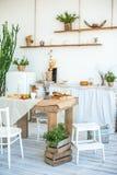 Kök i lantlig stil i sommar Fjädra ljus texturerat kök med en gammal kyl, trätabell Ett trämagasin med en vas, ska göra det arkivbild