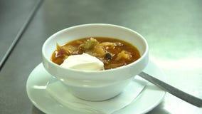 Kök Restaurang Kocken häller soppa i en bunke Dekoreras med kräm och gör grön stock video