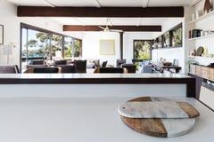 Kökbänk som ser för att öppna planvardagsrum i retro strand ho arkivbild
