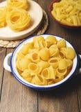 Kökbehållare med makaroni och spagetti omkring som ska lagas mat på trätabellen Royaltyfria Foton