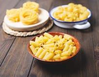 Kökbehållare med makaroni och spagetti omkring som ska lagas mat på trätabellen Royaltyfria Bilder