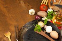 Kökjärnpanna och ingredienser som förbereder mål Träskedar för att laga mat Faciliteter av husmanskost Arkivbilder