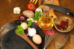 Kökjärnpanna och ingredienser som förbereder mål Träskedar för att laga mat Faciliteter av husmanskost Royaltyfria Foton