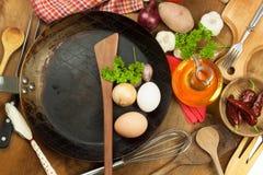 Kökjärnpanna och ingredienser som förbereder mål Träskedar för att laga mat Faciliteter av husmanskost Arkivfoto