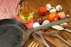 Kökjärnpanna och ingredienser som förbereder mål Träskedar för att laga mat Faciliteter av husmanskost Royaltyfri Bild