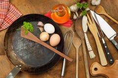 Kökjärnpanna och ingredienser som förbereder mål Träskedar för att laga mat Faciliteter av husmanskost Arkivfoton