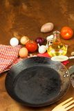 Kökjärnpanna och ingredienser som förbereder mål Träskedar för att laga mat Faciliteter av husmanskost Royaltyfri Foto