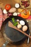 Kökjärnpanna och ingredienser som förbereder mål Träskedar för att laga mat Faciliteter av husmanskost Royaltyfria Bilder