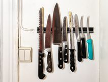 Kökknivar på magnetiskt holden på väggen arkivfoto