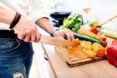 Kökkock, ledar- kock som förbereder matställen detaljer av bitande grönsaker för kniv i modernt kök Arkivfoto
