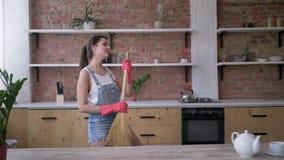 Köklokalvård, den lyckliga hemmafrun i grov bomullstvilloveraller och handskar dansar och lekar på kvasten som gitarren