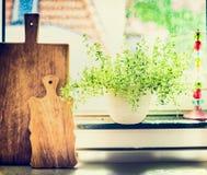 Kökmatlagningörter i blommakruka på fönster fortfarande med det cuting brädet Royaltyfria Foton