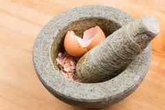 Kökmortel och mortelstöt med det kraschade äggskalet fotografering för bildbyråer