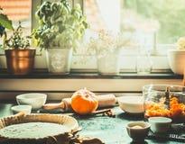 Kökplats med förberedelsen av traditionell festlig matlagning för pumpapaj på tabellen på fönstret royaltyfria foton